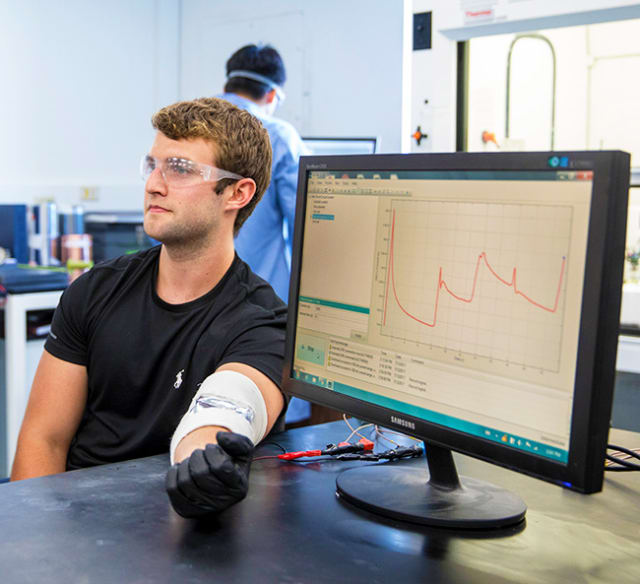 Vanderbilt undergraduate Thomas Metke demonstrates the ultrathin energy harvesting device which is taped across his elbow. As he flexes his arm the current the device generates is displayed on the computer display. (Image courtesy of John Russel/Vanderbilt University.)