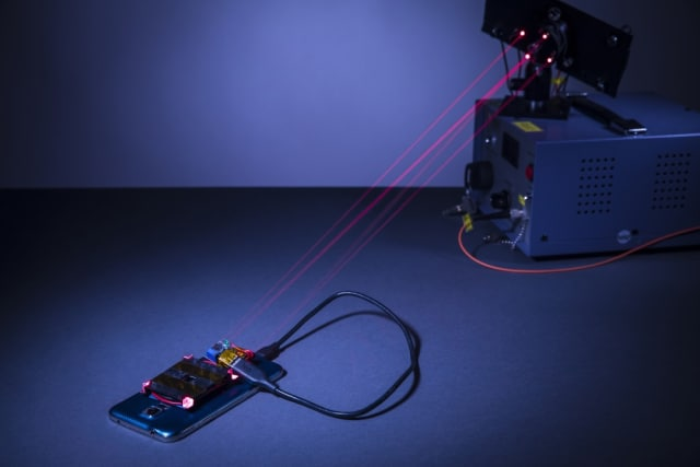 The wireless charging system created by University of Washington engineers. The charging laser and guard lasers are normally invisible to the human eye, but red beams have been inserted in place of the guard beams for demonstration purposes. (Image courtesy of Mark Stone/University of Washington.)