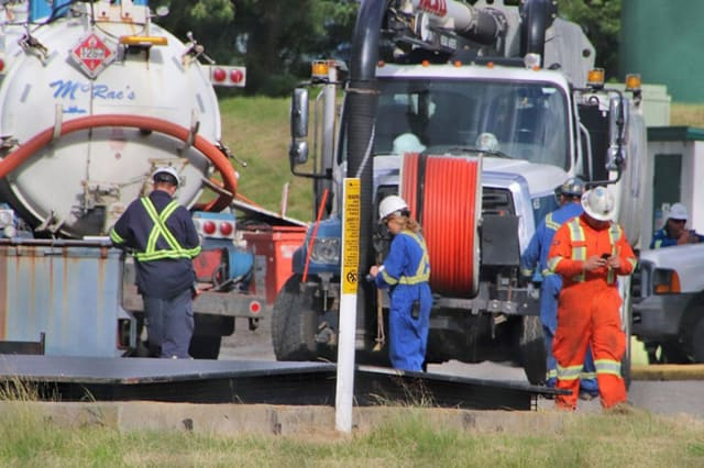 Workers recovering oil after a spill in Abbotsford, B.C. (Picture courtesy of The Abbotsford News.)