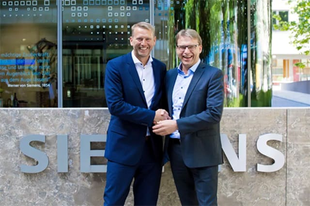"""""""A GODDAMN GOOD DIGITAL TWIN."""" Peter Carlsson (left), CEO of the battery manufacturer Northvolt, and Ulf Troedsson, executive advisor at Siemens Nordics. The connection between these companies makes it clear that Siemens will become a technology partner. The technical and commercial partnership includes two main areas of cooperation. First is Siemens' product range within the Xelerator PLM portfolio (NX, Teamcenter, Tecnomatix and more) and Siemens OpCenter on the OT side. Second is that Siemens intends to purchase batteries from Northvolt as soon as the large-scale production facility is completed 2023. During an event in Stockholm, Sweden, Peter Carlsson noted that the ongoing European battery factory battle is a tough arena where demand is soon expected to go through the roof. In ten years, he aims to take a 25-percent European market share. But this is a costly bet, because every GWh is surrounded by investments of around $100 million and in ten years the predicted need globally lies on the 3,000 GWh level. This means that Carlsson's Northvolt will have to invest for a total of 150 GWh capacity. How do you do that in an environment that is extremely complex in terms of product development and manufacturing building blocks? """"You build a goddamn good digital twin,"""" Peter Carlsson concluded."""