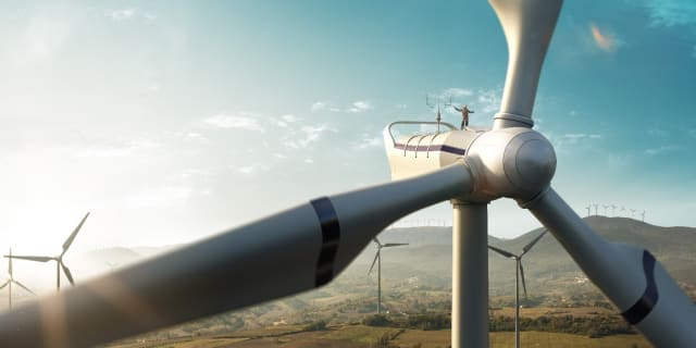 Green energy galore, but what of the energy used to create these massive machines? Look closely to see the human on top. (Stock photo)