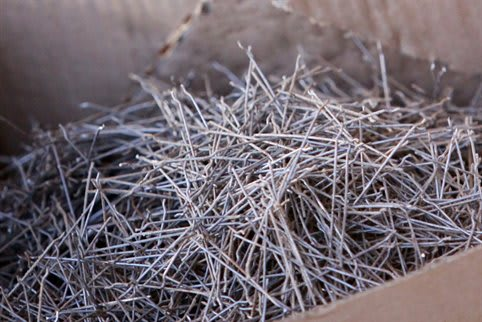"Steel wires, ready to be made into steel fiber-reinforced concrete. These ones have small deformations (""hooks"") at both ends to anchor them in the concrete (Image courtesy of CoGripedia.)"