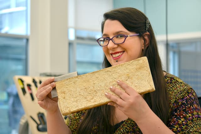 Sonia Travaglini measures a mushroom brick, which is a product of her research.
