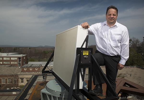 Michael Zink with the radar system installed at Marston hall. (Credit: UMass Amherst.)