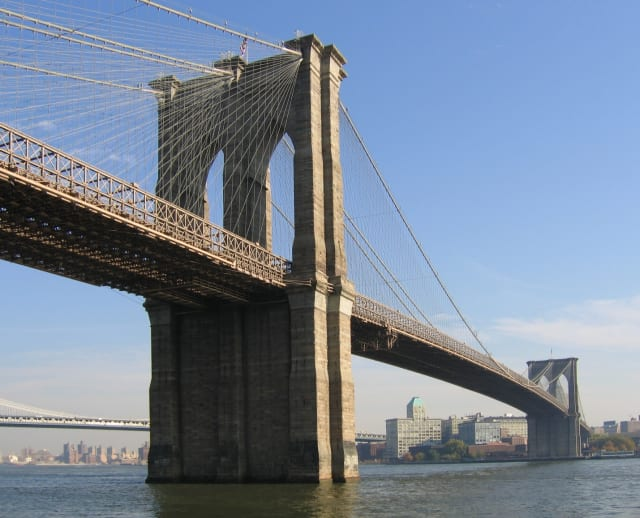 The Brooklyn Bridge, one of New York's most famous attractions, as seen from water level. One of the projects supported by the DoT's new round of BUILD funding is rehabilitating the bridge's masonry arches for the first time in more than a hundred years. (Image courtesy of Postdlf, Wikimedia Commons.)