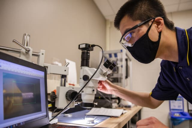 Yi Zhu, graduate student research assistant for civil and environmental engineering, tests the origami microbot. Photo courtesy of the University of Michigan.