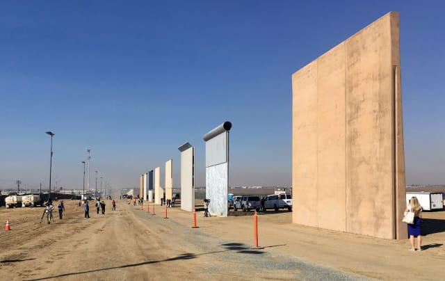 The border wall prototypes, immediately after their construction ended in 2018. A new government watchdog report suggests that the construction and decision process for the wall might be flawed. (Image courtesy of Elliott Spagat/AP.)