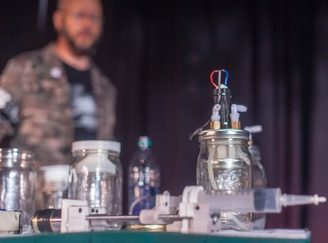 Michael Laufer (in the background) pictured with his Apothecary MicroLab. Laufer says that he has synthesized five different pharmaceutical drugs using his lab. (Image courtesy of Seth Rosenblatt, The Parallax.)