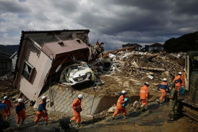 As the death toll climbs above 150, rescuers search for missing people in Hiroshima prefecture, western Japan. (Image courtesy of Sadayuki Goto, Associated Press.)