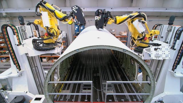 Figure 1. Robot arms at work: the robots connect fuselage parts of an aircraft with rivets. (Source: igus GmbH.)