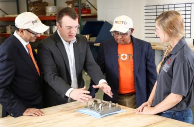 From left, John Johnson, Proto Precision; Ed Herderick, CDME; Sugu Suguness, Proto Precision; and engineering student Jordan Potts discuss the center's first nickel alloy print from the Concept Laser metal printer. (Image courtesy of Ohio State University, College of Engineering.)
