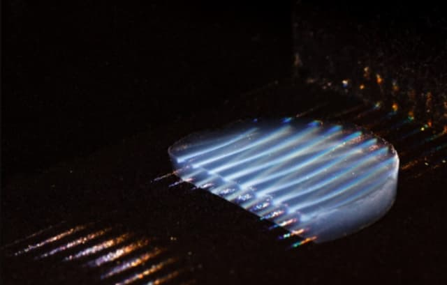 A new transparent aerogel insulating material, made visible in the photo using parallel laser beams, transmits 95 percent of sunlight. Researchers spent four years developing the silica-based material. (Image courtesy of MIT.)