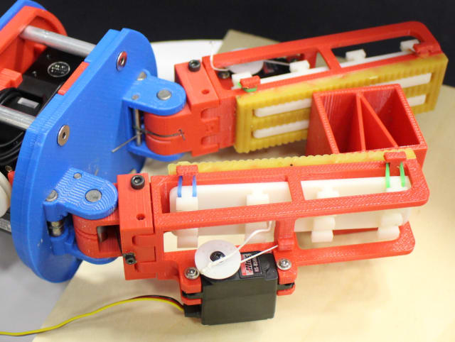 This gripper uses servos to retract the low-friction, rigid finger surface—a smooth, white surface—putting the object in contact with a high-friction deformable surface—yellow urethane rubber. (Image courtesy of GRAB Lab.)