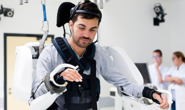 An exoskeleton controlled by a neuroprosthetic that records, transmits and decodes brain signals has made it possible for a teraplegic patient to walk and control his arms. (Image courtesy of Clinatec.)