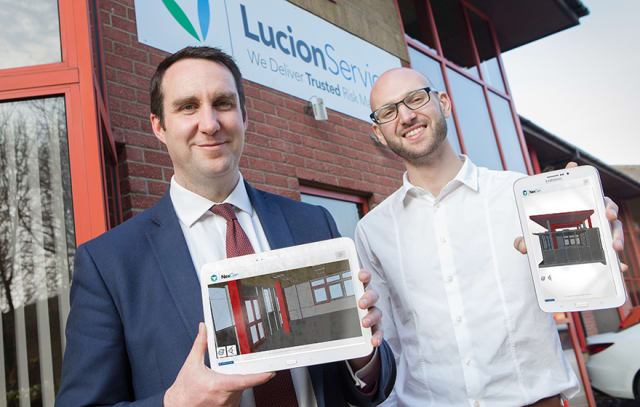 Lucion CEO Patrick Morton (left) with developer Alexei Holgate, who is partnering with the team to create an app that displays asbestos risk data. Both men are holding still images from their app. (Image courtesy of Lucion.)