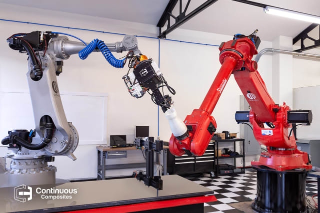 The robotic arm on the left includes the printhead, which pre-impregnates the reinforcement fiber with rapid-cure thermoset plastic that is instantly hardened as it is deposited on the print platform hosted by the robotic arm on the right. (Image courtesy of Continuous Composites.)