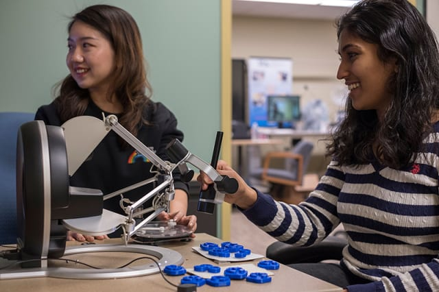 "HaptImage cofounders Ting Zhang (left) and Shruthi Suresh (right) use their system to ""touch"" and interact with digital blood cells on screen. (Image courtesy of Purdue Research Foundation image/Oren Darling.)"