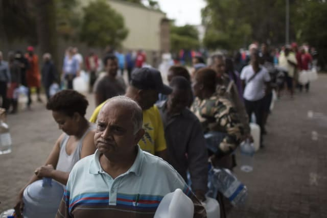Residents of Cape Town, South Africa, wait in line for water. (Image courtesy of AP Photo/Bram Janssen.)