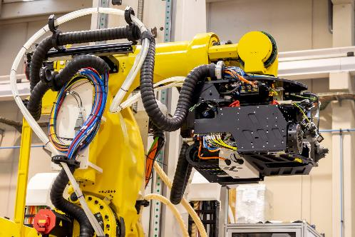 Figure 2. The cables for the tools on the end effector of the robotic arm are housed in black, three-dimensionally movable triflex chains and are safely guided by them. (Source: igus GmbH.)
