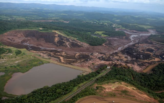 An aerial view of the collapsed dam (on the right) and the trail the mud carved through the surrounding countryside. (Image courtesy of Reuters.)