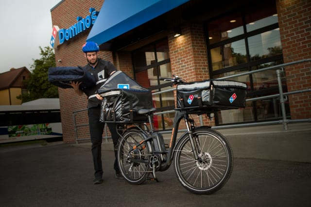 Cheaper by the dozen. Domino Pizza rolls out e-bike delivery. Modified Rad Power bikes fitted with the company's insulated cargo containers on the front and back with capacity for 12 large pizzas. (Picture courtesy of Domino.)