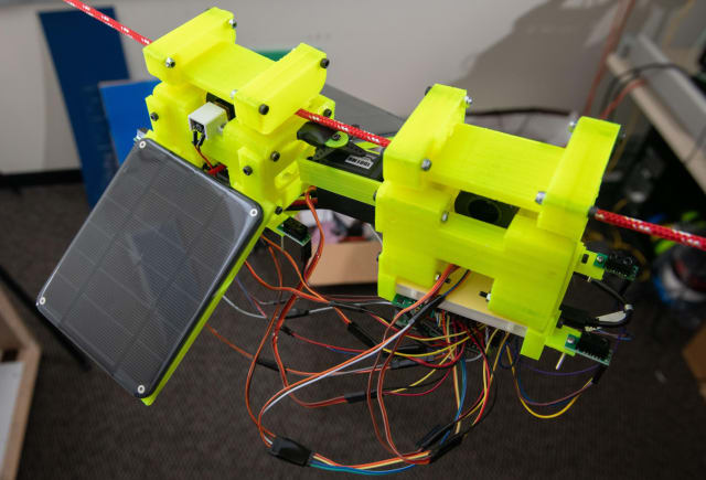 The SlothBot is powered by two photovoltaic panels: 3D-printed gears and switches that allow the robot to switch from one cable to another. (Image courtesy of Allison Carter/Georgia Tech.)