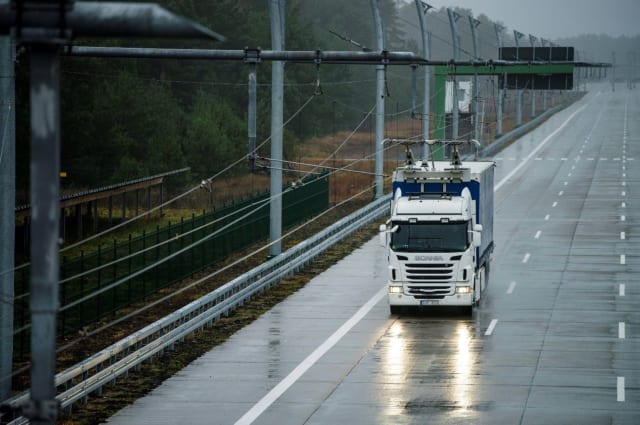 A hybrid truck operating in fully electric mode, powered by an overhead line electric road system in Germany.