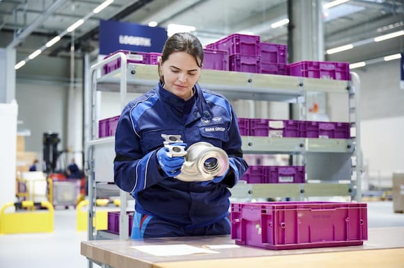 An associate inspects a metal additively manufactured component. (Image courtesy of the BMW Group.)