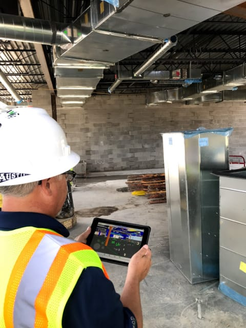 AECOM employee checks position of ductwork against the BIM model at the Walnut Grove Elementary School in Indianapolis, Indiana. Mobile devices and reliable data service are allowing blueprint to be replaced on construction sites.