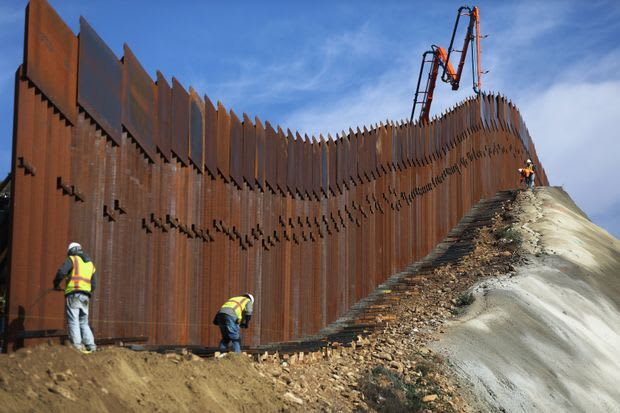 Construction workers putting up one segment of the new steel bollard wall. While the wall is inspired by the prototypes, the DHS claims that the border wall isn't directly based on any of them. (Image courtesy of Maria Tama, Getty Images.)