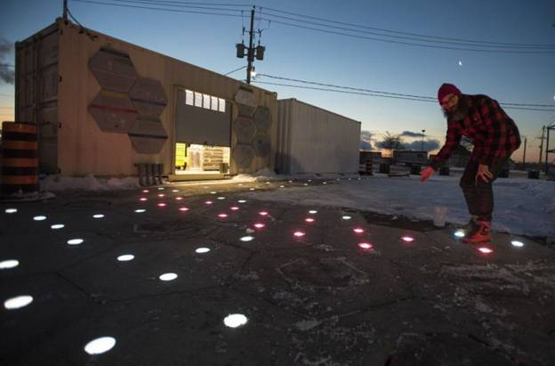 Sidewalk's Jesse Shapins shows off the project's new heated and lighted hexagonal pavement tiles, which are one of the innovations that the company hopes will make outdoor life in Toronto more pleasant during the winter. (Image courtesy of The Canadian Press/Tijana Martin.)