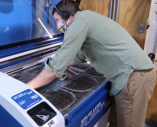 At the Boston Technology Center, a workshop team member uses a laser cutter to cut PET material for face shields. (Image courtesy of Autodesk.)