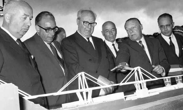 Riccardo Morandi (second from right) demonstrates a model of the Morandi Bridge to the then Italian president, Giuseppe Saragat (third from left), during the bridge's inauguration. (Image courtesy of Handout/AFP/Getty Images.)