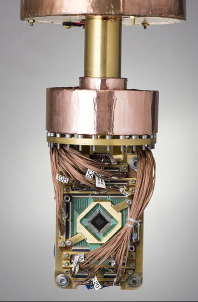 """The D-Wave 2000Q, also known as """"The Fridge,"""" is a closed-cycle dilution refrigerator, meaning the superconducting processor generates zero heat. It is 180 times colder than interstellar space! It's environment shielded to achieve an internal magnetic field 50,000 times less than Earth's. The superconducting processor generates no heat, is cooled to 180x colder than interstellar space, and consumes under 25kW of power. (Image courtesy of D-Wave.)"""