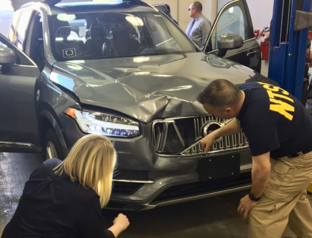 NTSB officials inspect Uber's Volvo XC-90, damaged from where it struck a pedestrian in a fatal accident. (Image courtesy of the AP.)