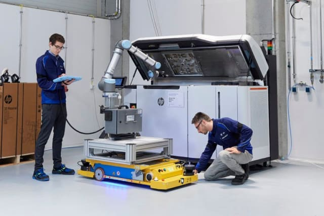 Associates demonstrate automation work with a robotic arm and a HP Multi Jet Fusion system at the Additive Manufacturing Campus. (Image courtesy of the BMW Group.)
