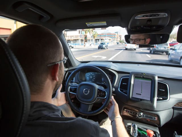 Uber mounts its operator's console in the center of the vehicle, with the top of the console slightly above the dash of the Volvo XC-90, as shown in this picture from Wired. Below the console is what appears to be the driver's smartphone with the screen on. Note that the driver is covering the steering wheel with both hands. (Image courtesy of Natalie Behring, Reuters.)