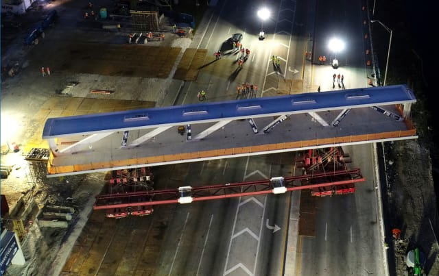 Accelerated bridge construction (ABC) techniques used for the FIU bridge. The prefabricated main section main span (which was later to collapse) was fabricated nearby and is shown here being moved into place in a five-hour overnight operation while SW 8th St was closed to traffic. (Image courtesy of Miami Herald.)