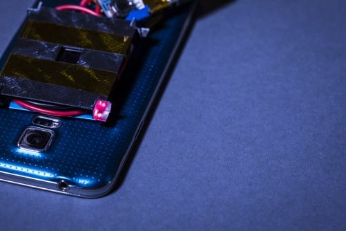 Illuminated in red is one of the 3-D printed retroreflectors, which reflects the low-power guard beams to diodes on the laser emitter. Interruption of the guard beams triggers a safety system which blocks the charging beam. (Image courtesy of Mark Stone/University of Washington.)