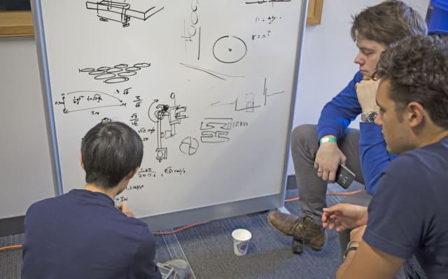 Dennis Zhang, a mechanical engineering concentrator, does some initial hand calculations for his team's robotic throwing arm. (Photo by Alana Davitt/SEAS Communications.)