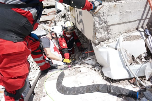 The Robotics Institute's Matt Travers, center, in white vest, works with red-suited Mexican Red Cross workers to prepare a snake robot to enter a collapsed apartment building in Mexico City. (Image courtesy of Carnegie Mellon.)