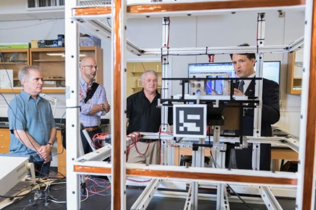 Brian Gunter, assistant professor in Georgia Tech's Guggenheim School of Aerospace Engineering, shows the small satellite testing facilities in his lab to Xenesis leadership. Shown (l-r) are Neal Campion, Xenesis Strategy Director; Mark LaPenna, Xenesis CEO and founder; Mike Carey, chief strategy Officer at Atlas Space Operations, and Gunter. (Image courtesy of Allison Carter/Georgia Tech)