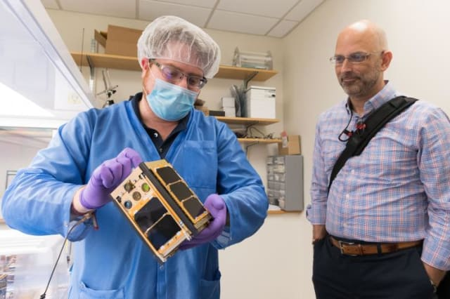 Georgia Tech aerospace engineering graduate student Byron Davis shows Xenesis CEO Mark LaPenna one of the RANGE CubeSats scheduled to go into orbit later this fall. (Image courtesy of Allison Carter/Georgia Tech).