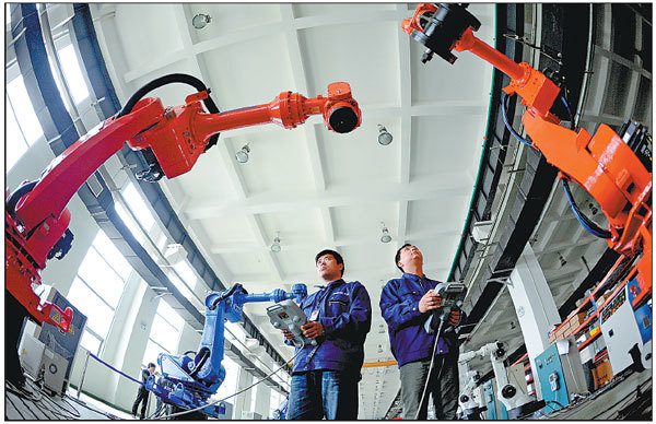 Workers test industrial robots at a Siasun Robot & Automation Co Ltd plant in Shenyang, Liaoning province.