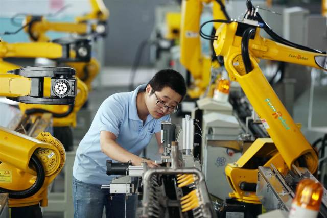 A factory worker tests robot arms at a plant belonging to Zhejiang EverRobot Robotics Co., Ltd. in Jiaxing, China. (Image courtesy Shen Zhicheng / Imaginechina via AP)