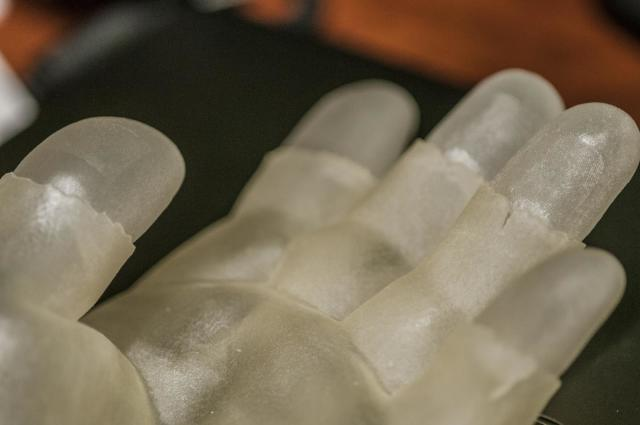 MSU researchers demonstrate how a 3-D printed model hand is used to test a fingerprint scanner for accuracy. (Image courtesy of G.L. Kohuth.)