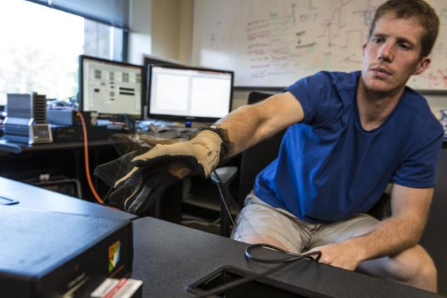 CSNE M.D./Ph.D. student and GRIDLab member David Caldwell tests the hardware used for stimulating and recording a patient's brain surface, along with a cyber glove to track hand joint angles and finger motions. (Image courtesy of Mark Stone/University of Washington.)