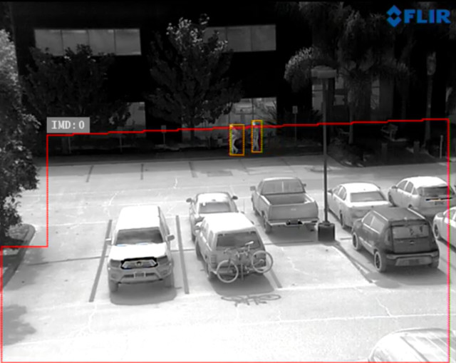 An infrared security camera identifies two people in a parking lot. (Image courtesy of FLIR.)