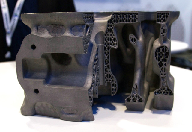 The part optimized for 3D printing features a complex interior geometry that reduces weight and improves performance.