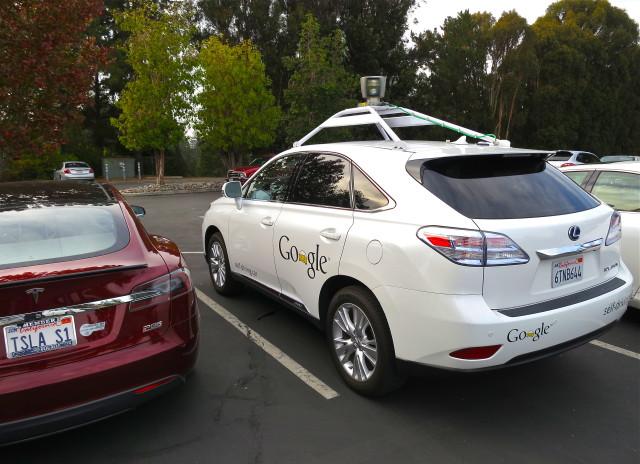 Lexus RX450h retrofitted by Google for its driverless car fleet. At the left side is parked a Tesla Model S electric car. (By Steve Jurvetson [CC BY 2.0 (http://creativecommons.org/licenses/by/2.0)], via Wikimedia Commons)